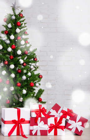 stock photo winter concept gift boxes and decorated christmas tree with colorful balls over white brick wall