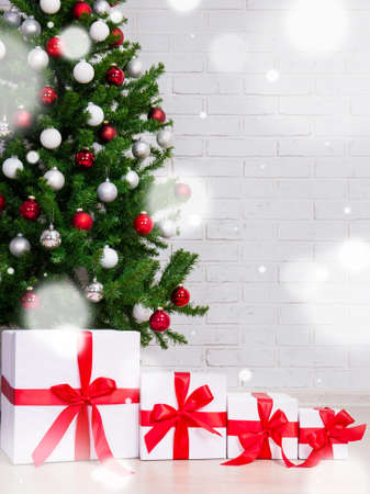 christmas background - gift boxes under decorated christmas tree over brick wall and flying snow flakes Zdjęcie Seryjne - 85450477