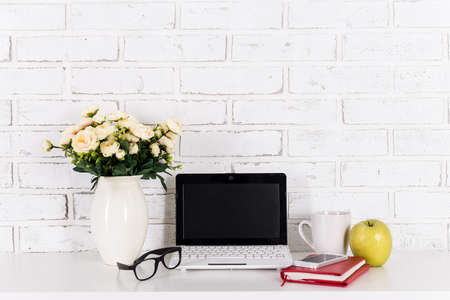 front desk: workplace with modern laptop on the table over white brick wall background Stock Photo