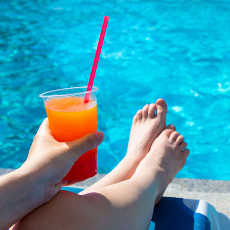 summer, travel and vacation concept - female hand holding colorful cocktail over swimming pool background Stock Photo