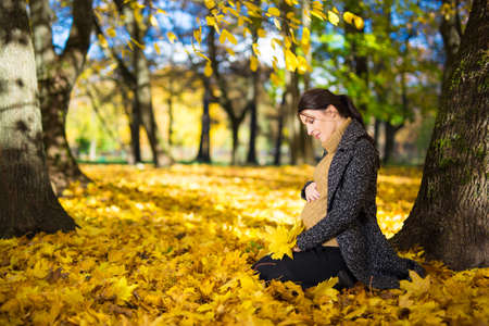 happy young pregnant woman sitting in autumn park