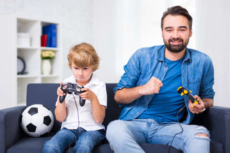 winner and loser - young father and son with gamepads playing video game at home
