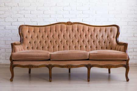 brown retro sofa over white brick wall Фото со стока