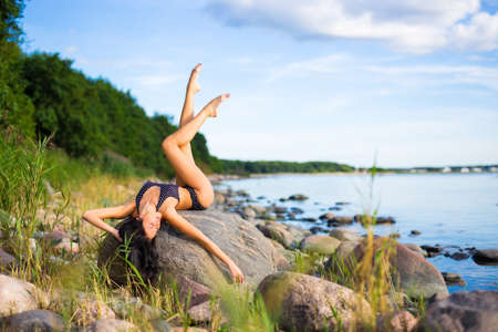 young beautiful model in swimsuit posing on rocky beach Stock Photo