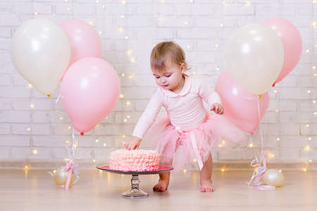 birthday celebration - funny little girl smashing cake over brick wall background with lights and colorful balloons