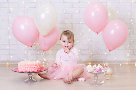 first birthday - cute little girl eating cake over brick wall background with lights and colorful balloons