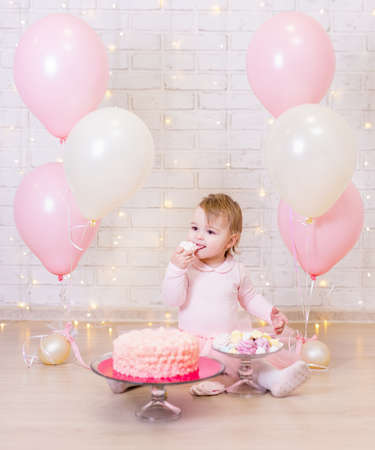 birthday party concept - cute little girl eating cake over brick wall background with lights and pink balloons Foto de archivo