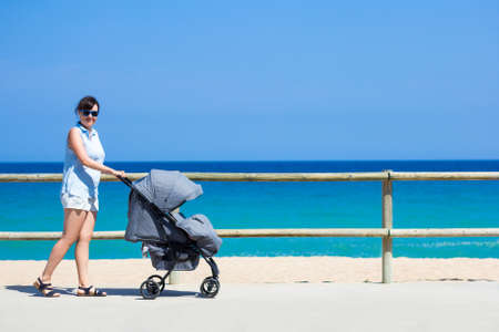 parenting and travel concept - side view of young mother pushing baby stroller on the summer beach
