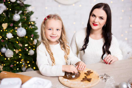 Portrait of happy mother and little daughter cooking gingerbreads in kitchen with decorated Christmas tree Banco de Imagens