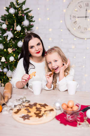 cute little girl and her mother cooking and eating Christmas cookies or gingerbreads in decorated kitchen