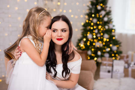 portrait of happy daughter whispering secret or christmas gift wishes to her mother in decorated living room with christmas tree Standard-Bild