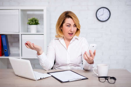 angry mature business woman with smart phone in modern office