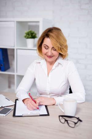 Concepto de plan de negocios - alegre mujer de negocios madura que trabaja en la oficina, escribiendo algo en el portapapeles