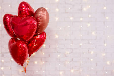 Valentine's day background - group of red heart shaped balloons over white wall with shiny lights