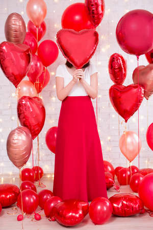 valentine's day concept - full length portrait of woman covering her face with red heart-shaped balloon