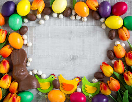 Easter frame background - close up of colorful eggs, decorative chicks, tulips, chocolate bunny and sweets