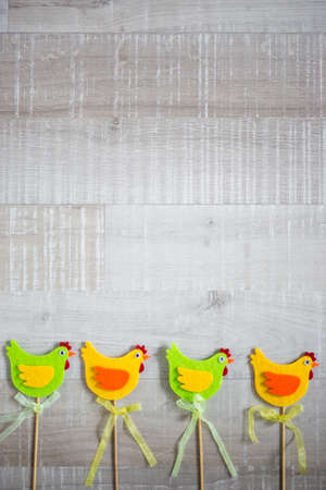 Easter concept - colorful chicks over wooden table background
