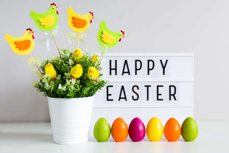 Vintage lightbox with happy Easter greetings, flower pot and colorful painted eggs