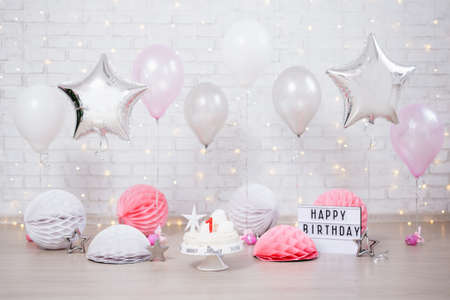 first birthday background - cake, helium balloons and lightbox with happy birthday text Stock Photo