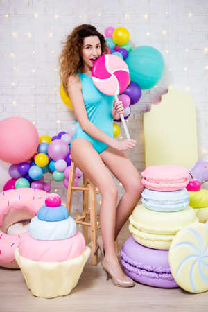 full length portrait of young woman in blue bodysuit posing with giant pastry decorationg