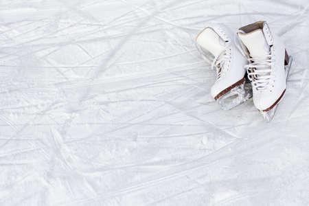 Cerca de patines blancos y copie el espacio sobre fondo de hielo con marcas de patinaje