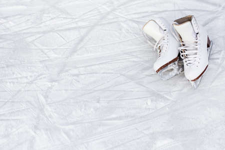 close up of white figure skates and copy space over ice background with marks from skating