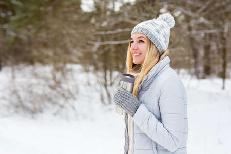 portrait of young blond woman in winter park or forest with thermo cup of coffee