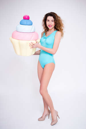 full length portrait of young woman in swimsuit posing with giant cupcake over gray background