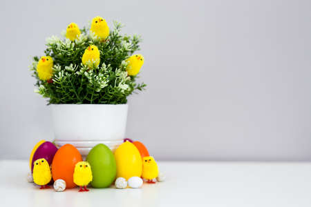 Flower pot with green plant and colorful Easter decorations on the table with copy space