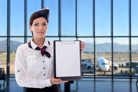 summer, vacation and travel concept - beautiful stewardess holding blank clipboard in airport