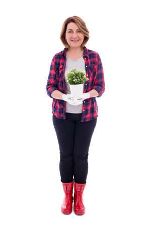full length portrait of smiling mature woman gardener with potted plant isolated on white background