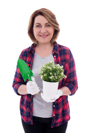 portrait of mature woman gardener with potted plant and shovel isolated on white background