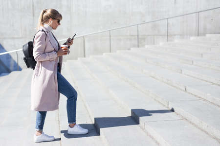 success and career concept - side view of young woman with smart phone walking up the stairs Standard-Bild