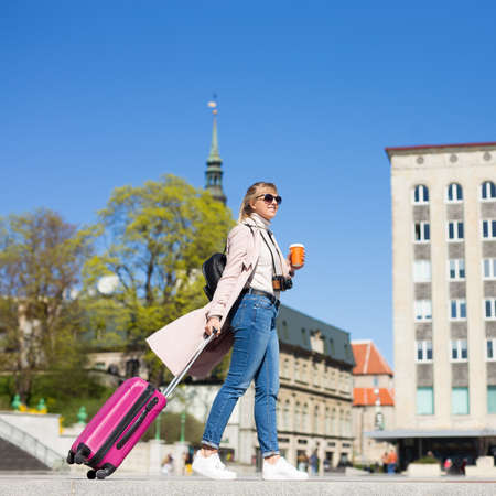 summer vacation, tourism and travel concept - woman with suitcase walking in old town of Tallinn, Estonia Stock Photo