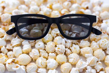 cinema concept - close up of 3d glasses over popcorn background