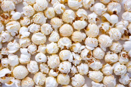 food and entertainment background - close up of crunchy salted popcorn