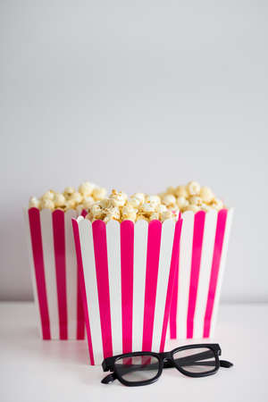 cinema concept - popcorn in red striped boxes and 3d glasses with copy space Imagens