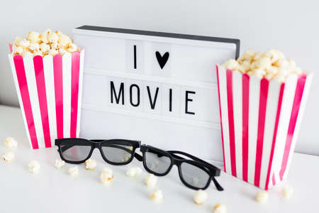 cinema concept - close up of pink striped boxes with popcorn, 3d glasses and light box with I love movie text 版權商用圖片