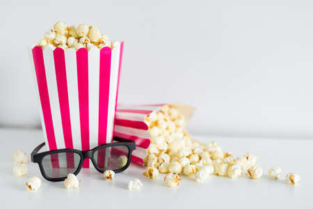 close up of striped boxes with popcorn, 3d glasses and copy space over white background