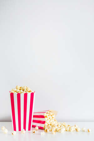 striped boxes with popcorn and copy space over white background Imagens