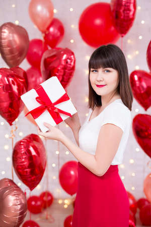 valentine's day concept - young beautiful woman holding gift box over red heart-shaped balloons background Banque d'images - 123119242