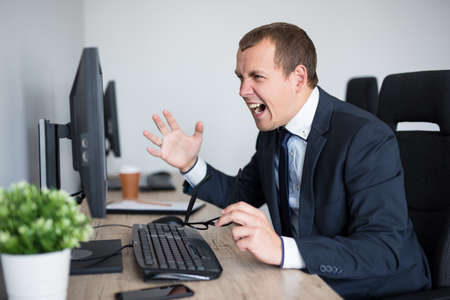 portrait of angry stressed businessman screaming on his computer in modern office