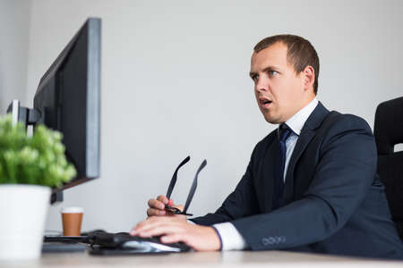 portrait of young surprised or shocked business man using computer in modern office