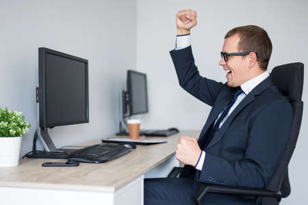 business and success concept - portrait of young successful business man celebrating something in modern office Reklamní fotografie