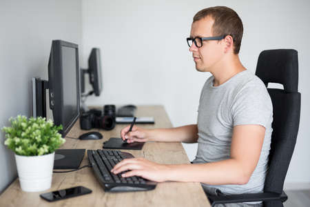 portrait of young handsome male photographer and retoucher editing images with computer in modern bright office 写真素材