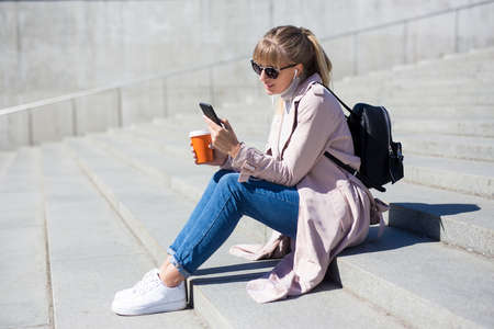 lifestyle and travel concept - outdoor portrait of young woman sitting on stairs with smartphone and paper cup of coffee