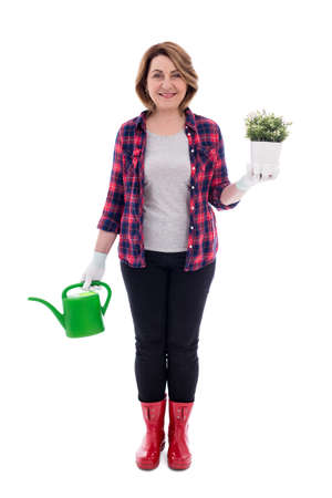 full length portrait of smiling middle aged woman gardener with potted plant and watering can isolated on white background