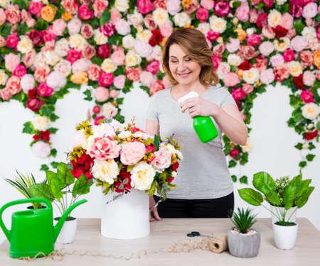 portrait of happy mature female florist or gardener working in flower shop Banco de Imagens - 124962466