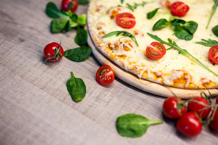 close up of pizza with tomatoes and herbs and copy space on wooden table background 스톡 콘텐츠