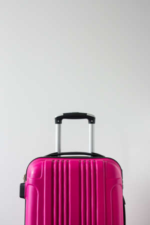 travel background - big pink plastic suitcase over white background with copy space Reklamní fotografie